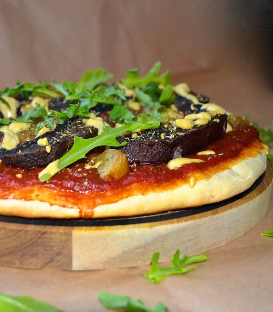 a vegan portobello and roasted garlic pizza on a round wooden board