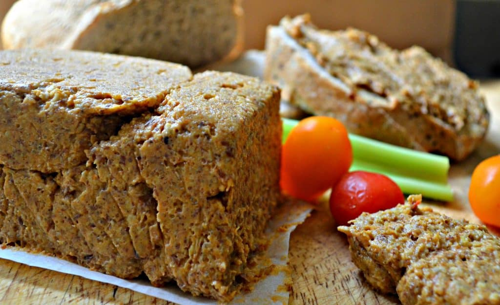 vegetable pate on a a board with cherry tomatoes and raw celery