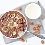 A mouthwatering baked oatmeal with a deliciously crusty exterior and a soft, creamy, chocolatey oaty interior, crunchy roasted hazelnuts and soft, sweet baked banana.