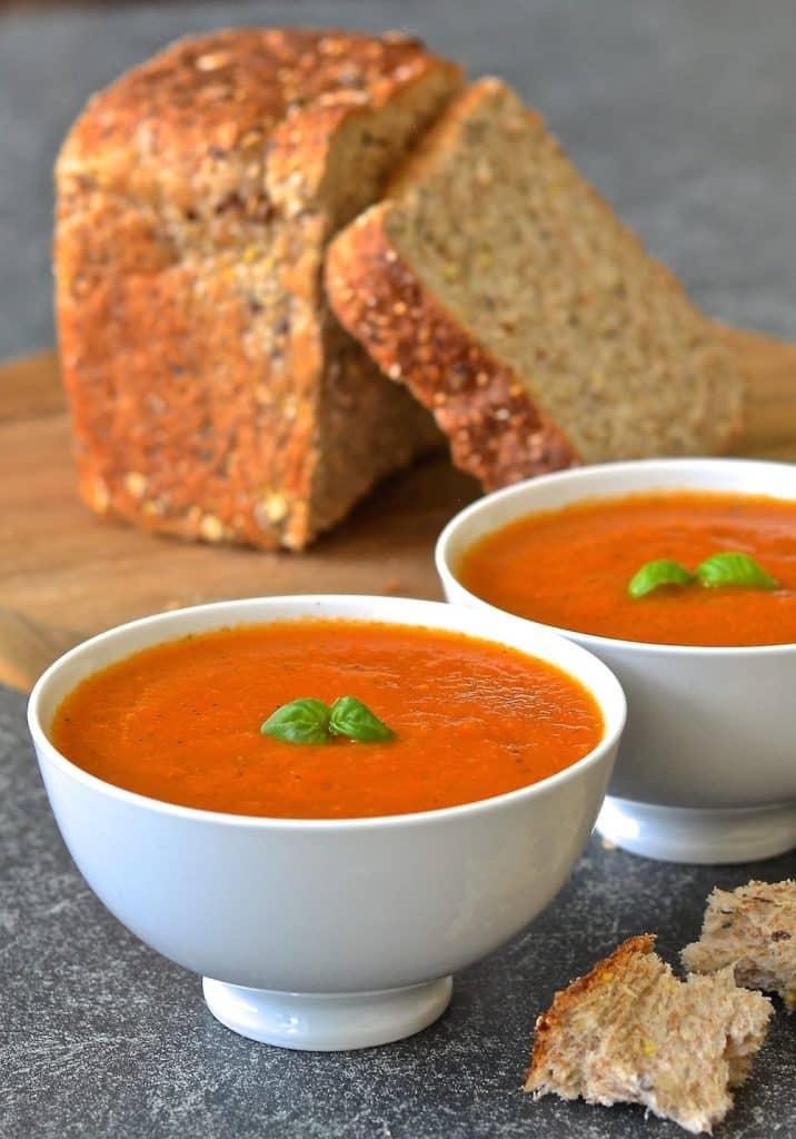 Easy Tomato Basil Soup in bowls, topped with fresh basil. A loaf of cut bread in background.