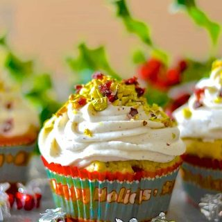 Festive, fragrant & delicious Pistachio Cranberry Orange Muffins! Orange scented, studded with juicy, jewel red cranberries & crunchy, vibrantly green pistachios & finished with a swirl of vanilla cream.