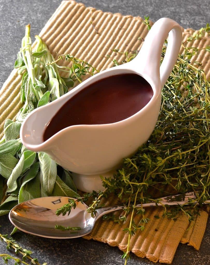 Red Wine Vegan Gravy in a gravy boat with fresh herbs scattered around