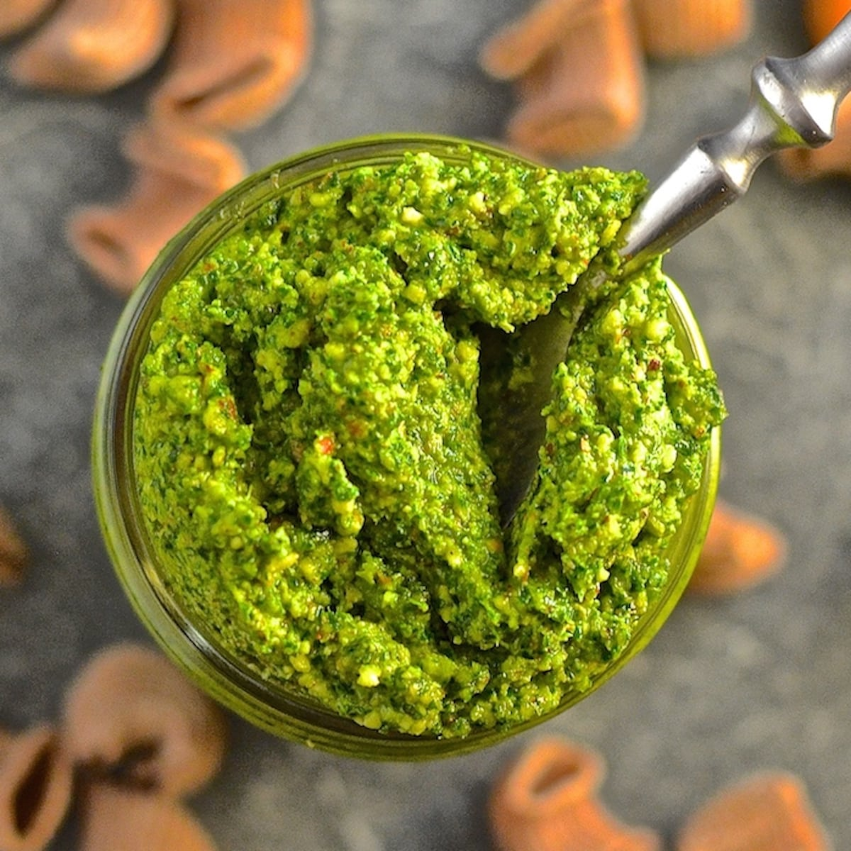 a jar of kale almond pesto with a spoon in it. Photo taken from above.