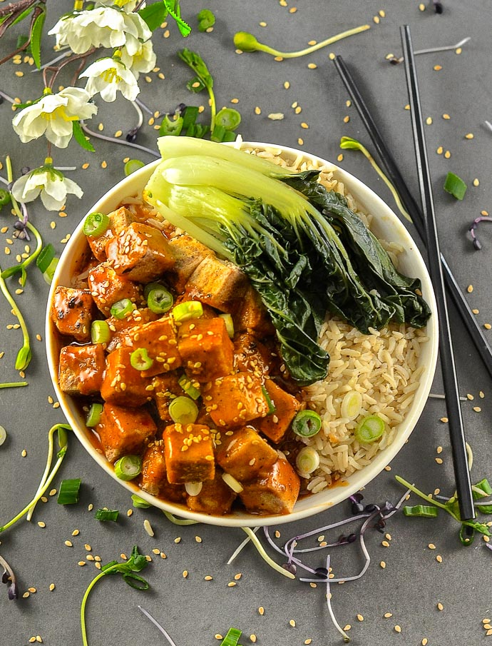 Five Spice Tofu with Chili Ginger SAuce in a bowl with rice and bok choy. Chopsticks to the side and cherry blossoms and sesame seeds scattered around