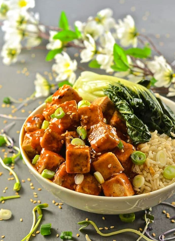 Five Spice Tofu with Chili Ginger Sauce in a bowl with bok choy. Cherry blossom in background and a scattering of sesame seeds all around.