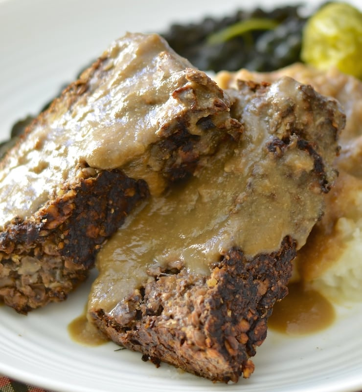 close up shot of vegan meatloaf on a plate with gravy
