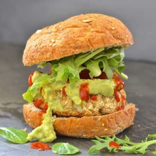 a whte bean artichoke burger in a wholewheta bun with lettuce, guacamole and hot sauce