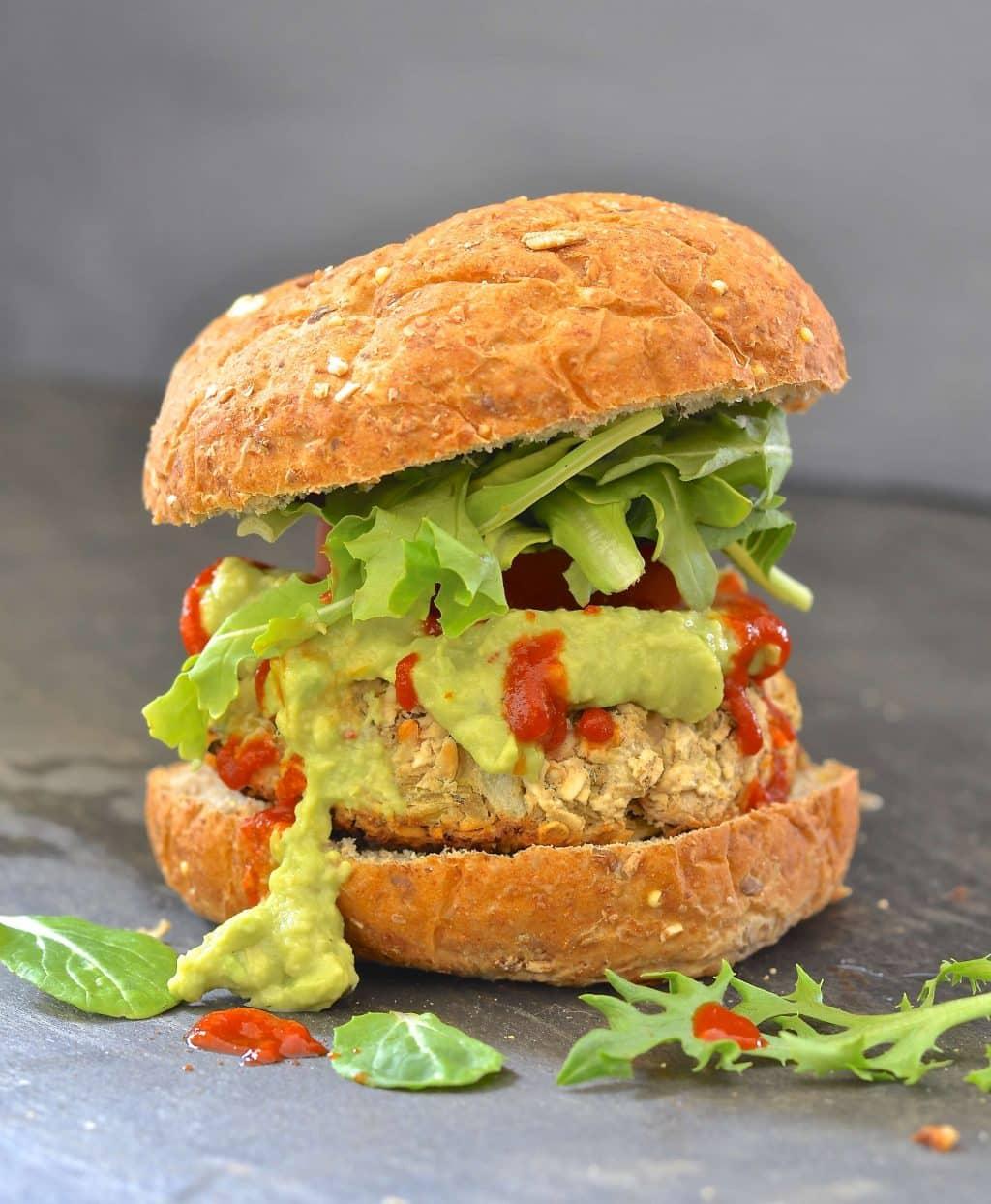 a whte bean artichoke burger in a wholewheta bun with lettuce, guacamole and hot sauce