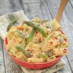 Creamy Asparagus Lemon Pasta Salad in a red bowl on a rustic wood backdrop