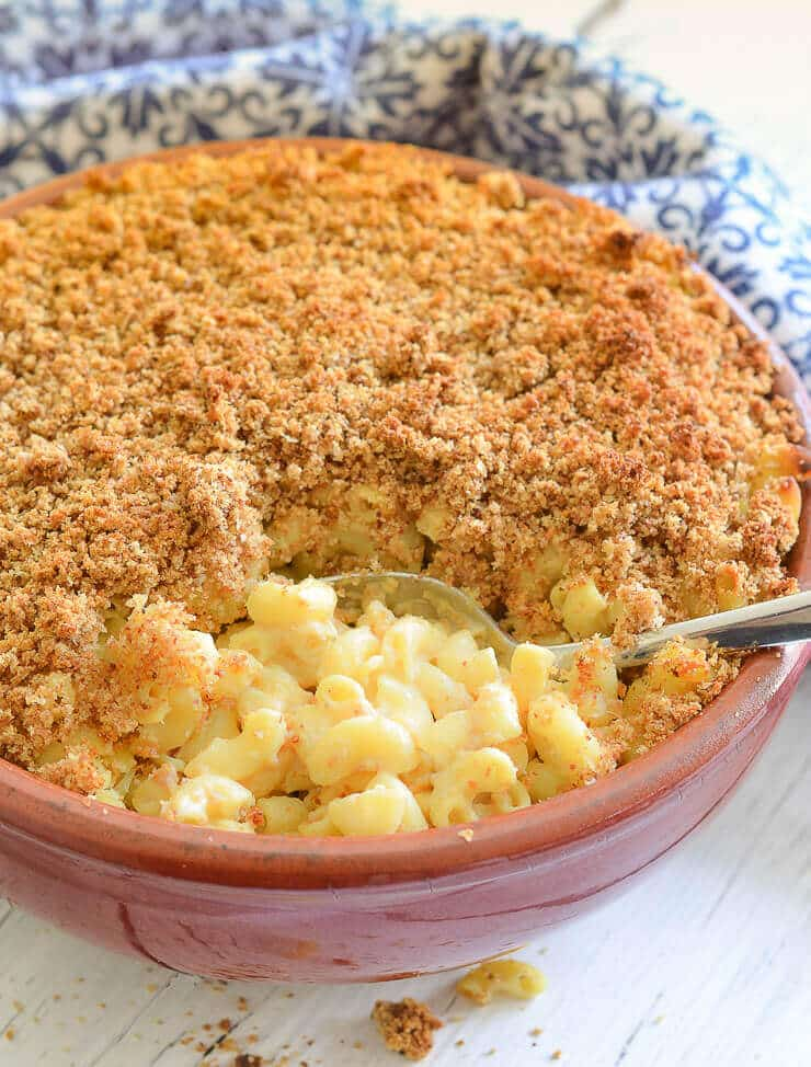 The ultimate Baked Vegan Mac and Cheese with a buttery, crunchy topping all in a terracotta dish! Shot taken with a big spoonful taken out and the creamy mac and cheese visible underneath the crumb top