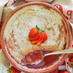 baked strawberry semolina pudding with piece cut out and spoon resting in bowl