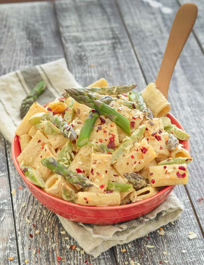 Creamy Asparagus Lemon Vegan Pasta Salad in a red bowl on a rustic wood backdrop