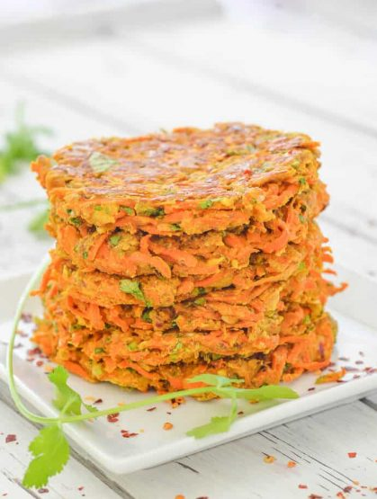 Stacked Curried Carrot Fritters with cilantro garnish