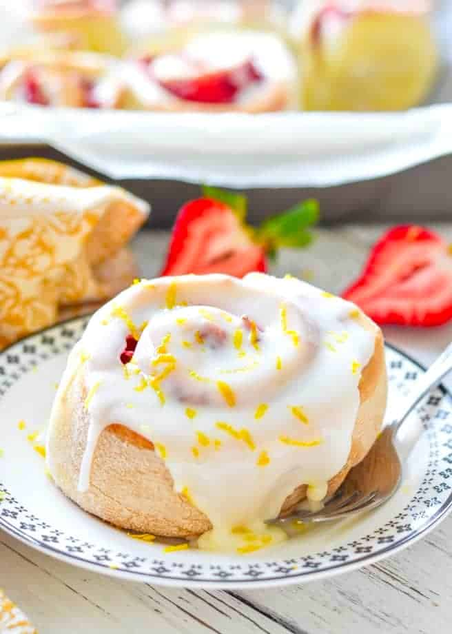 a lemon strawberry roll covered in frosting and lemon zest on a small plate