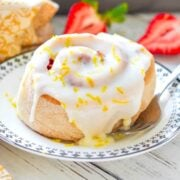 a lemon strawberry sweet roll on a small plate with a fork beside it