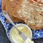 easy vegan butter in jar with knife resting on top with a slice of buttered bread to the side
