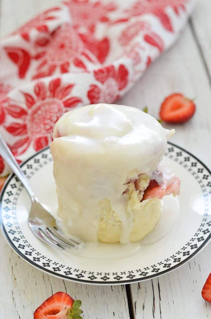 Strawberry Sweet Roll Mug Cake on a plate with white frosting