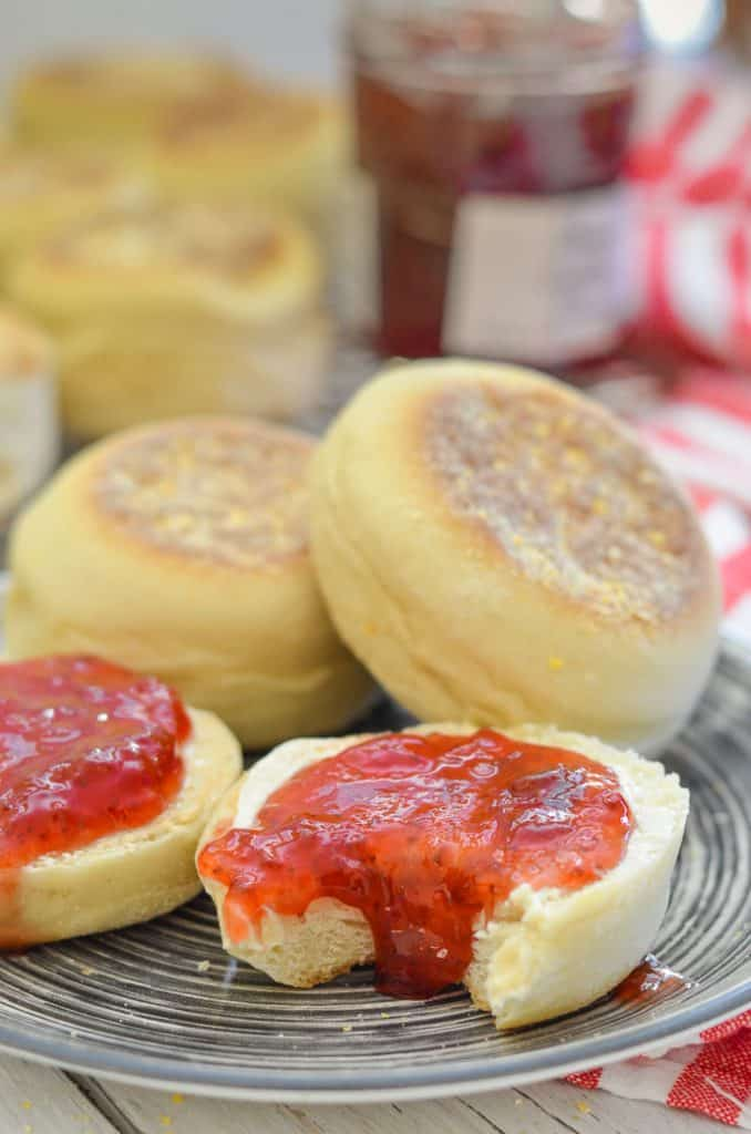 Close up Shot of Homemade English Muffins on a plate. Split, spread with drippy jam with a bite taken out.