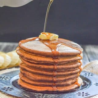 Vegan Gingerbread Pancakes with a knob of butter on top & maple syrup pouring over