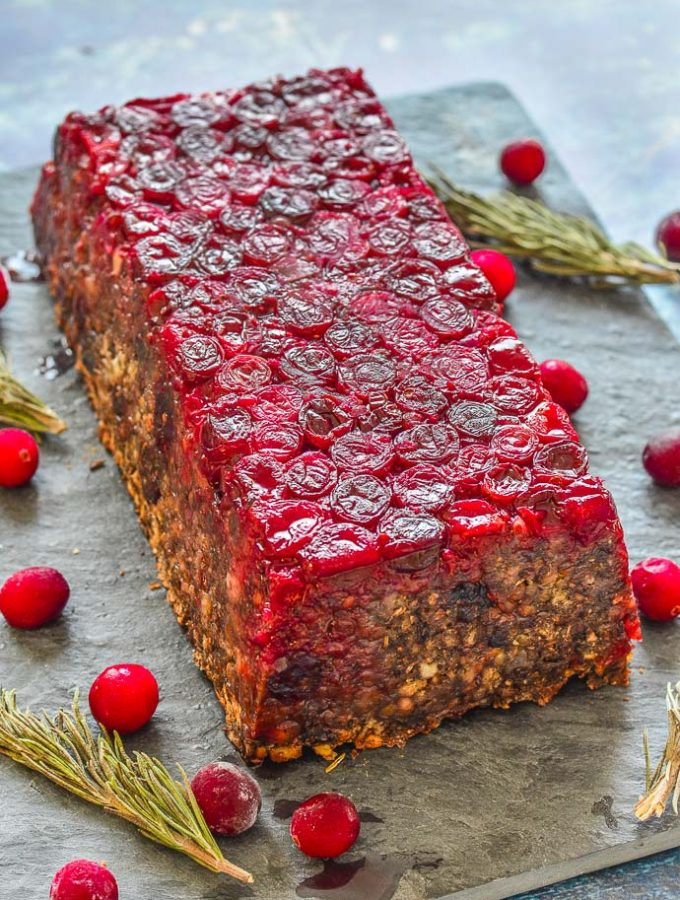 Mushroom Lentil Loaf with Cranberry topping turned out on a slate board and surrounded by scattered cranberries and rosemary