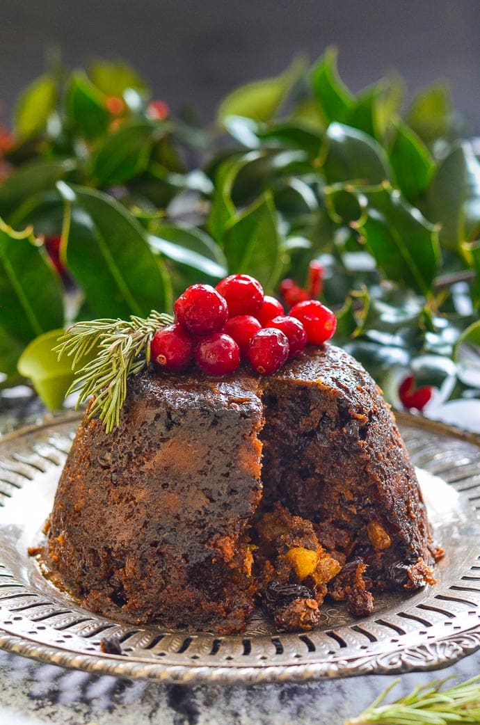 Vegan Christmas Pudding with a wedge cut out and inside showing.