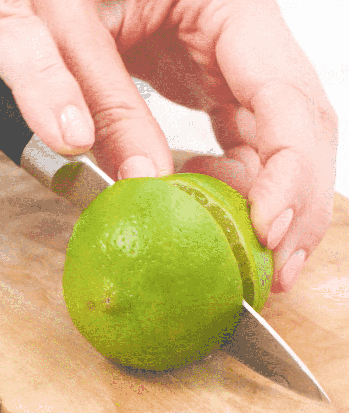 a lime being cut in half on a wooden board