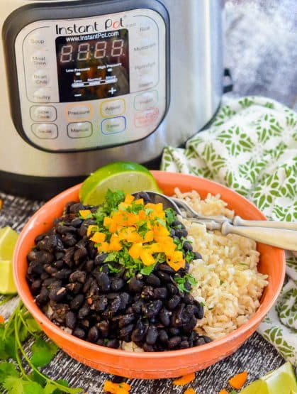 Seasoned Pressure Cooker Black Beans in a bowl over rice with the Instant Pot in the background