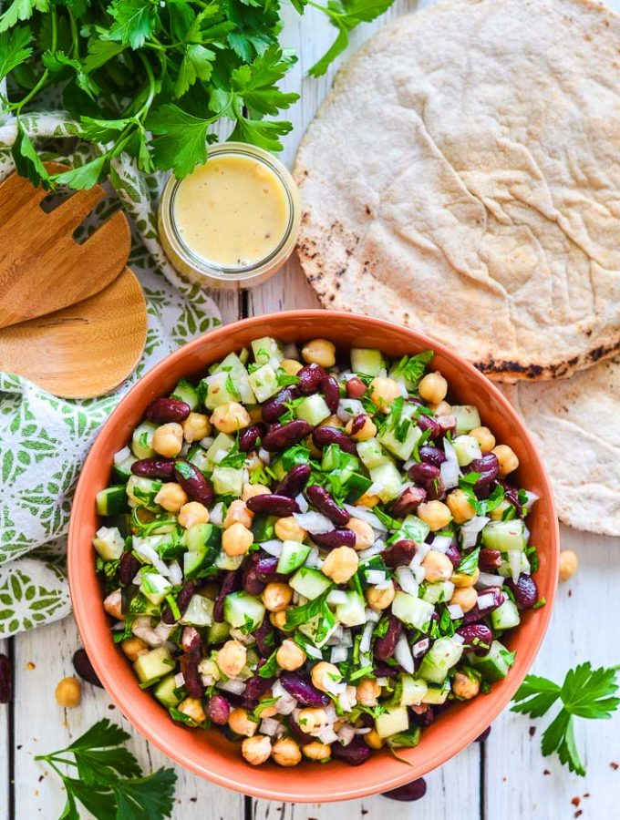 Kidney Bean Salad in a terracotta bowl. Photograph taken from above with pita bread, a pot of lemon dressing and a bunch of parsley