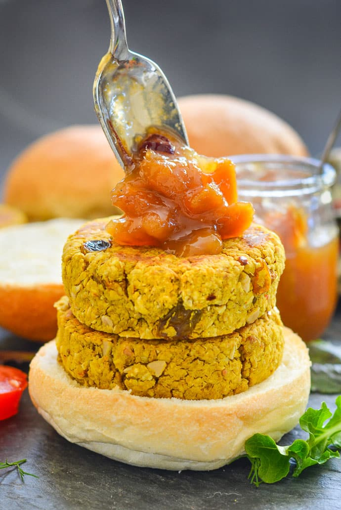 two curried chickpea burgers stacked on a bun with a generous spoon of mango chutney being dolloped on top