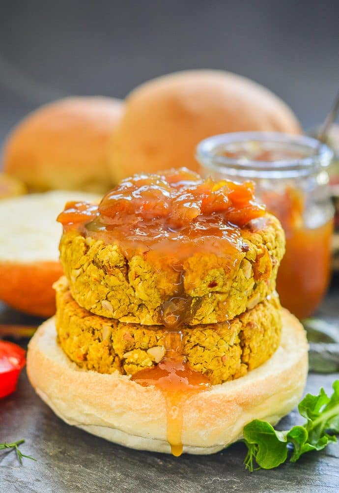 curried chickpea burgers stacked on a bun with a dribble of mango chutney running down the side