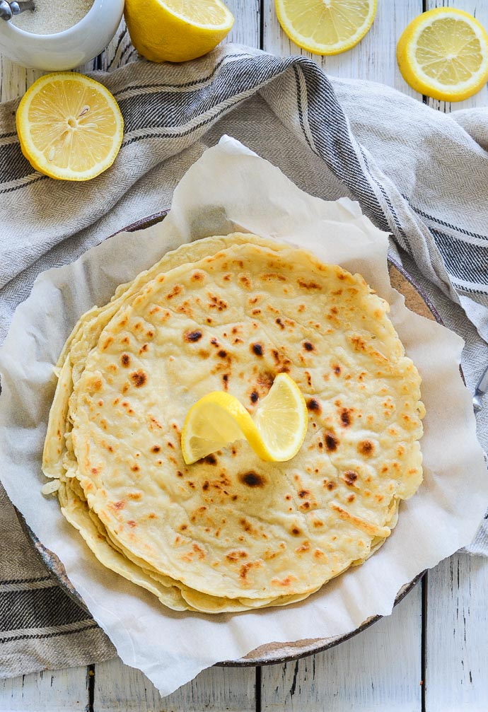 Vegan English Pancakes piled on a plate with a twirl of lemon
