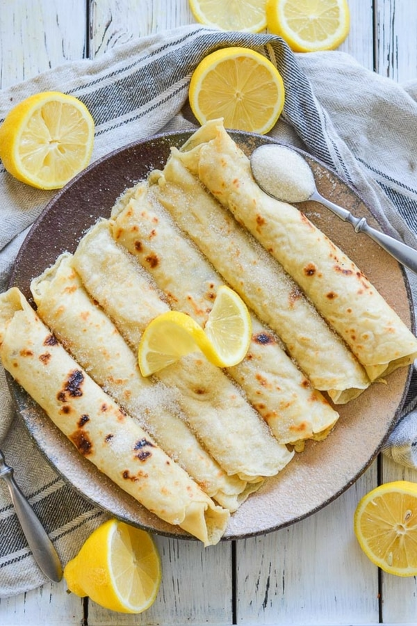 Foolproof Vegan English Pancakes. Quick & easy to make & great for dessert or brunch! They are beautifully freckled and so good straight from the pan, served glistening with fresh lemon juice & sugar. #pancakes #veganpancakes #englishpancakes #pancakeday #shrovetuesday #fattuesday