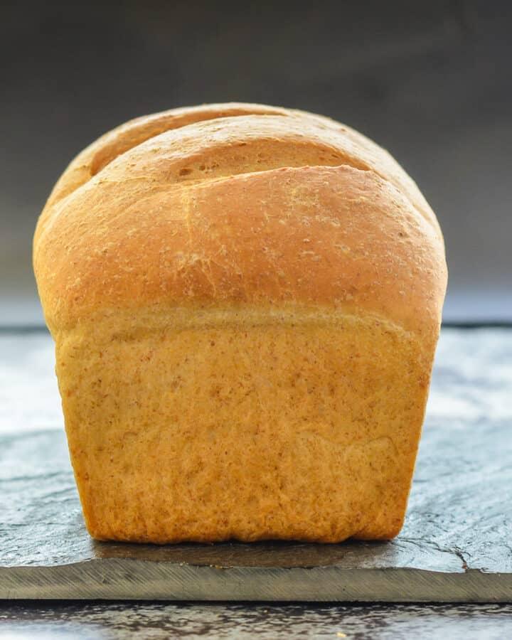 an uncut loaf of crusty bread on a slate board