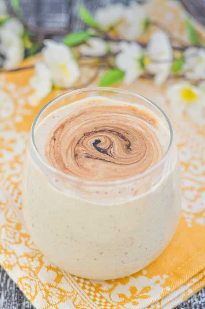 Creamy Banana Smoothie in a glass with a swirl of date syrup on top