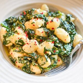 Vegan Gnocchi and kale in a creamy sauce and sprinkled with red pepper flakes and freshly ground black pepper
