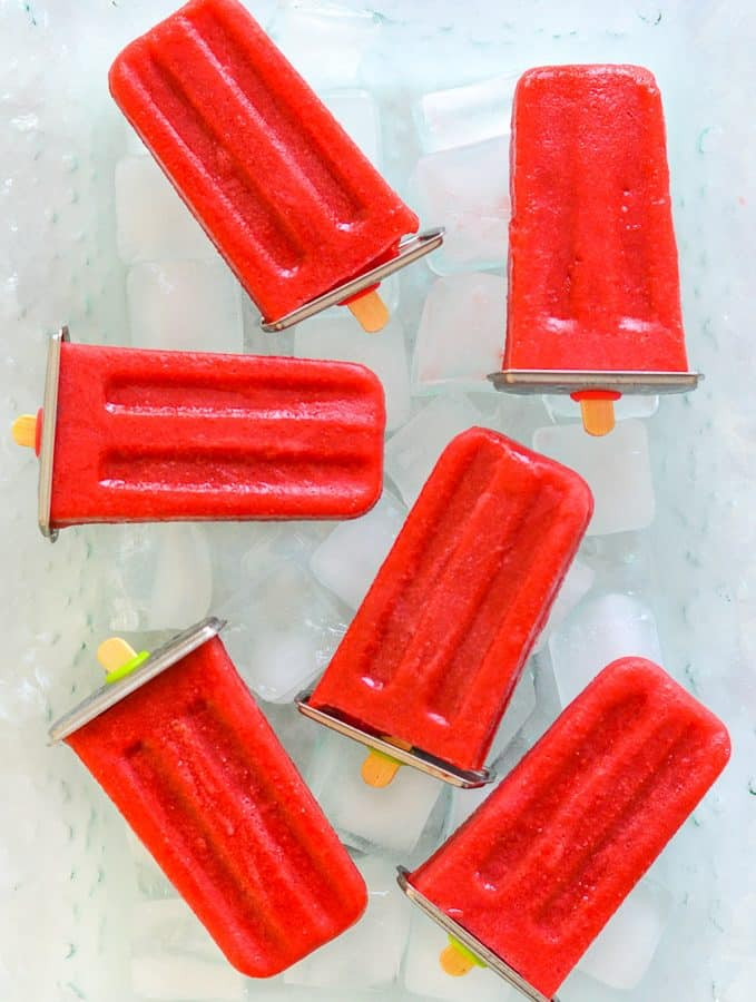 strawberry popsicles laid out on ice cubes