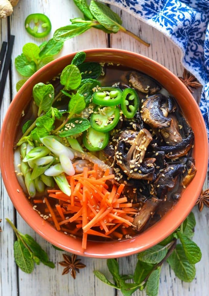 Udon Noodle Soup topped with mushrooms, carrot, green onions, jalapeno and sesame seeds