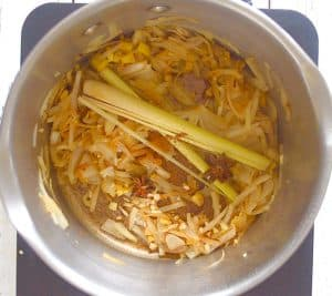 onions, garlic, lemon grass, cinnamon & star anise in a pan - making udon noodle soup