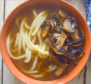 udon noodles, broth and mushrooms in a bowl