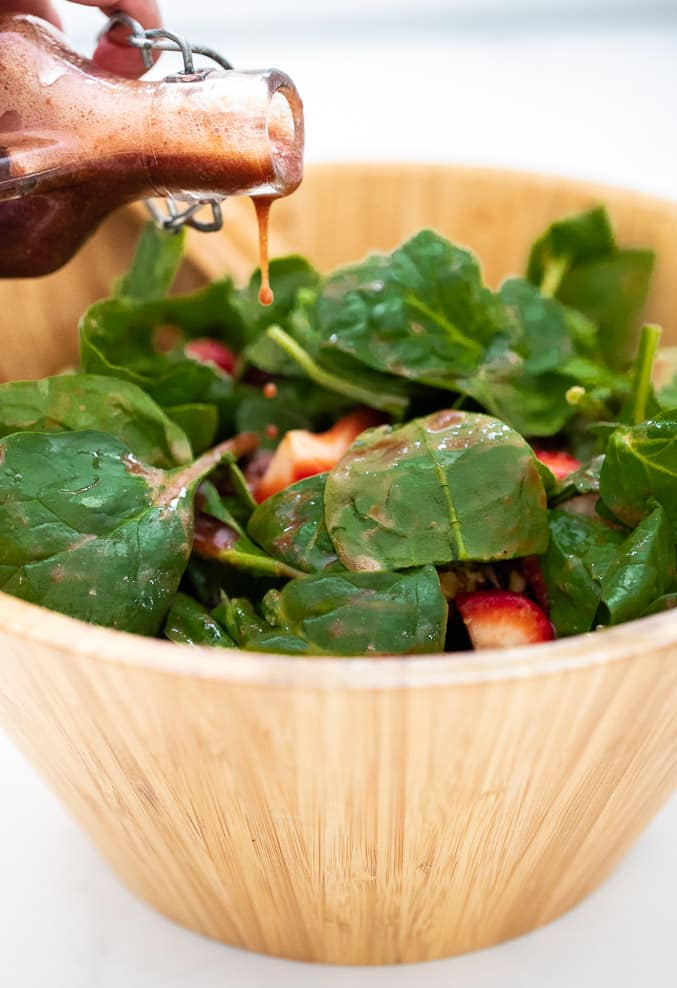 Strawberry vinaigrette being drizzled over leafy greens