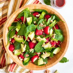 strawberry spinach salad in a wooden bowl