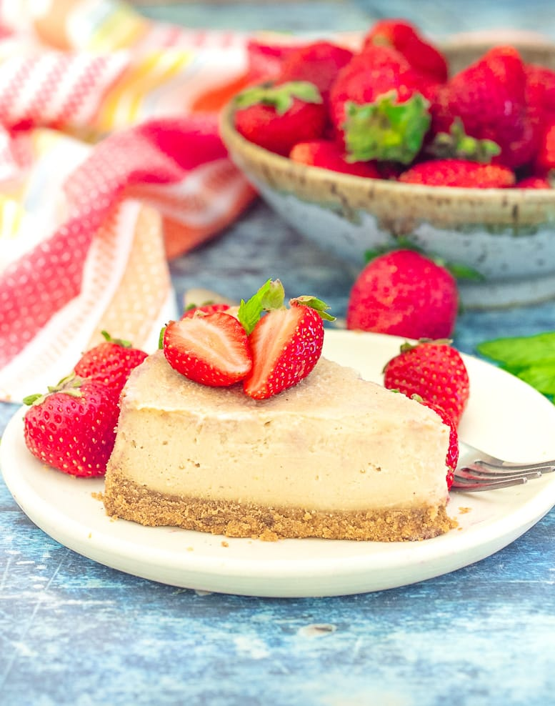 a slice of Vegan New York Cheesecake on a plate with strawberries