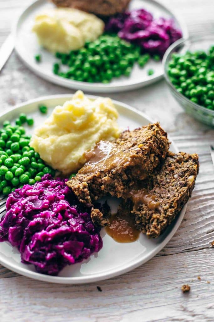 vegan meatloaf sliced on a plate with mashed potato, gravy and vegetables