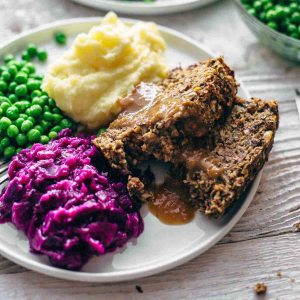 vegan meatloaf, mashed potato, red cabbage and peas on a plate