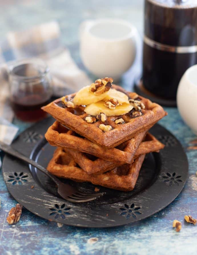 banana waffles stacked on a plate with maple syrup, walnuts and sliced banana
