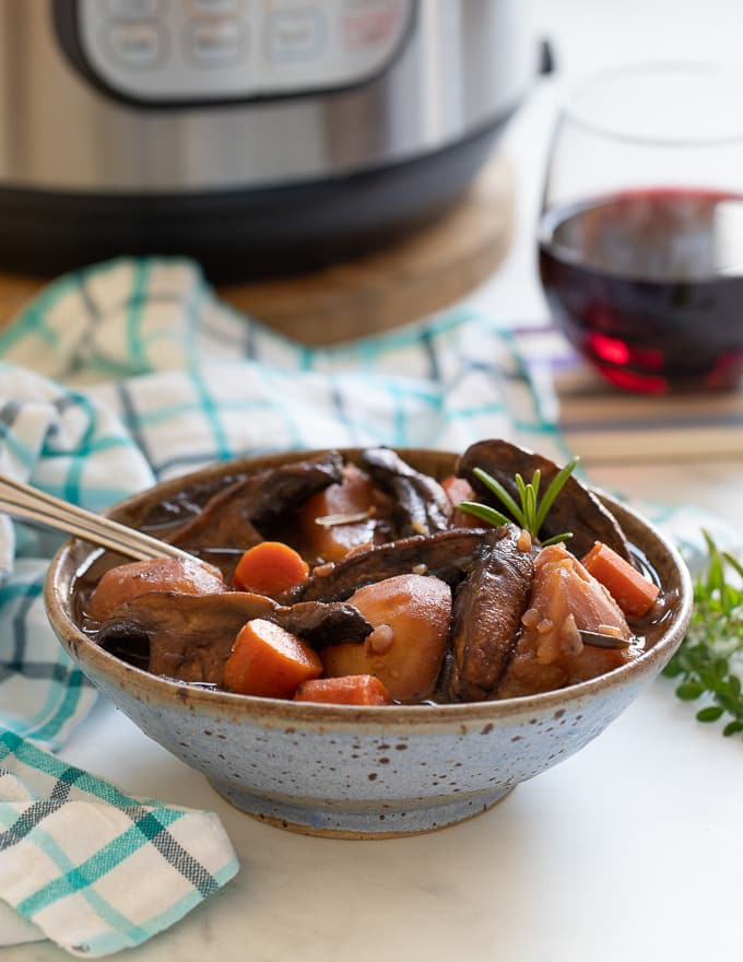 Vegan Portobello Instant Pot Pot Roast in a bowl with an Instant Pot and glass of red wine in the background