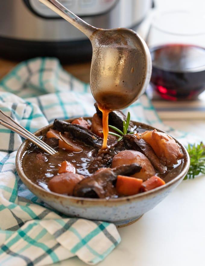 Vegan Portobello Instant Pot Pot Roast being ladled into a bowl