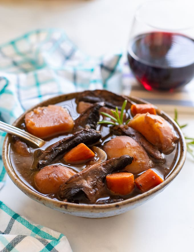 Vegan Instant Pot Portobello Pot Roast served in a bowl with a sprig of fresh rosemary