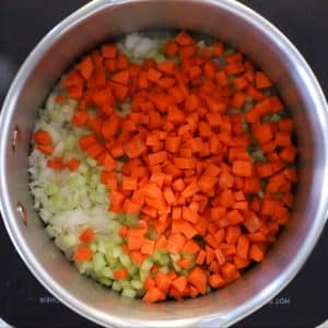 onion, celery and carrot sautéing in a pan - ready to make vegan potato soup