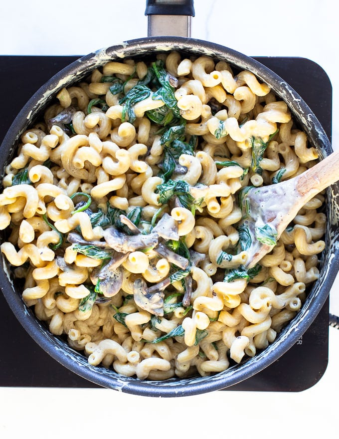 Creamy Vegan Mushroom Pasta in a pan with a wooden spoon